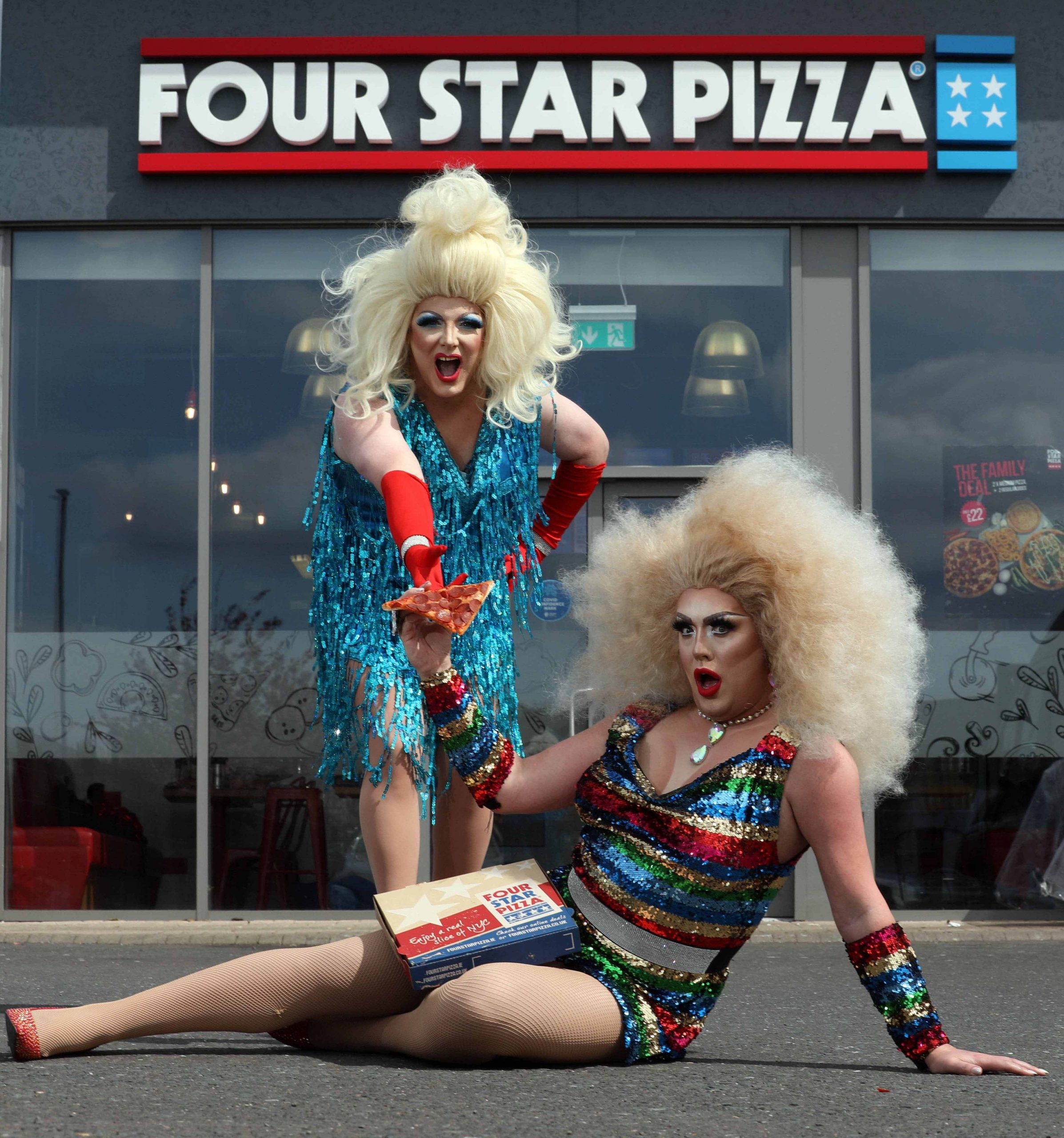 """Pizza fanatic, Alfie Parker (38) (blue dress), a mechanic from Belfast, had no idea when he responded to a message from his favourite pizza takeaway, that he would become Northern Ireland's latest Drag Queen, Anita Pizza, following a makeover by NI Drag Queen royalty, Trudy Scrumptious! Alfie, aka Anita Pizza, said: """"I didn't think my love of Four Star Pizza would lead me down this path, and in heels, but my outlook on life is that you only live once, so after discussing it with my wife, Isobel, and daughter Brianna, I decided to give it a go."""" Brian Clarke, Director at Four Star Pizza, explained: """"We wanted to do something a bit different for the launch of our new pizzas; everyone knows how amazing our pizzas are, it wasn't about that, we just wanted to stop our customers in their tracks with something surprising that would put a smile on their faces."""" Visit www.fourstarpizza.co.uk for more information and details of their new menu."""